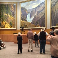 Cowboy hall of fame residents looking at tryptic of yellowstone park