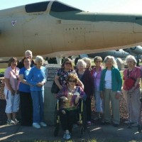Tinker outing with residents in front of a plane