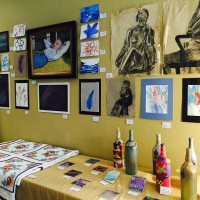 Art show with charcoals by darline wine bottles and coasters