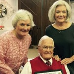 Dr. Dean Robertson with daughters Sally and Rindy, showing his Centenarian Certificate.