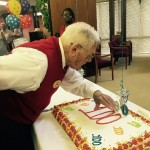 Blowing out his candles on one of his huge sheet cakes!