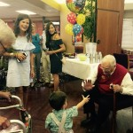 Greeting guests, grandkids, and great grandkids at his party.