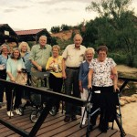 The group crossing the bridge over the creek on the grounds at the