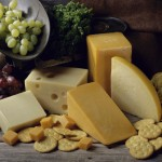 Close-up of cheese with crackers and grapes