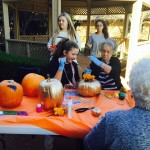Mary Kate and Wanda making holes in their gold pumpkin to insert flowers. By the way, the front of the pumpkin says,