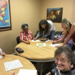 Arts council teachers instructing the residents in how to do the embossing.