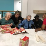 Residents and associates packing saltine crackers.