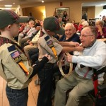 Boy Scouts pinning flag pin on Bill Rodgers.