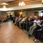 Veterans on the first and second rows on each side of the room.