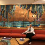 Wanda sitting in front of the big mural in the lobby with copper, turquoise, gold, lots of geometric shapes.