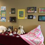 Various mediums of art including quilt and knitted afghan.