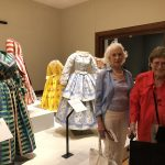 Betty and Mable in front of some of the older dresses worn in the era of Queen Elizabeth I.