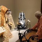 Sue Ann looking at some of the dresses inspired by airplanes and boating in the early 1900's.