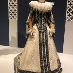 One of the most beautiful gowns in the whole collection, showing a full lace collar, beading all over the dress that looks like silver, lace cuffs, and jewelry. The paper hair is braided into a typical style for the era.