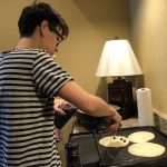 Marco adding blueberries or chocolate chips to the pancakes.