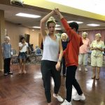 Heritage Hall student, Marco turning Chelsea, the instructor and following through to continue dancing.