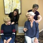Sharon and Karen getting chair massages from Kaitlan and Trish.